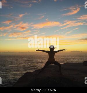 Woman doing yoga on the cliff - Stock Photo