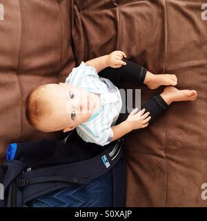Little baby boy sitting on the couch - Stock Photo