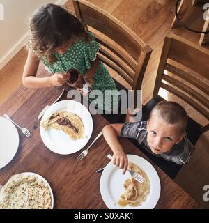 Little boy and little girl eating breakfast - Stock Photo