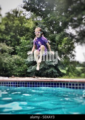 Girl wearing purple suit and swim goggles jumping into a swimming pool - Stock Photo