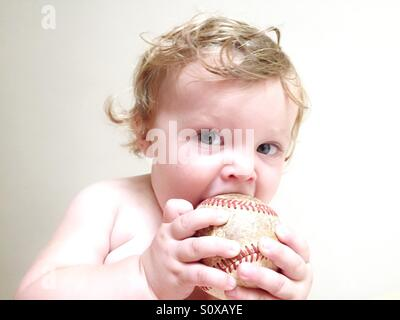High key image of a baby boy chewing on an old baseball