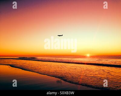 Jet flying over the Atlantic Ocean during sunrise in Myrtle Beach South Carolina. - Stock Photo