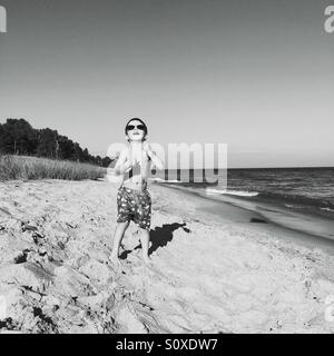 Back and white image of a young boy wearing sunglasses flying a kite on the beach. - Stock Photo