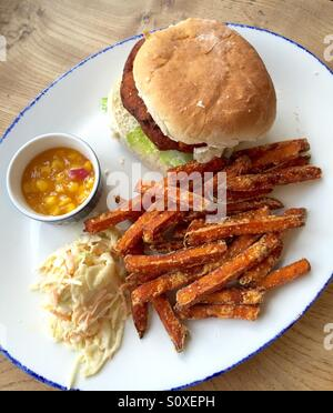 Vegetable burger served on a white bap with sweet potato fries, coleslaw and sweetcorn relish - Stock Photo
