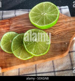 Sliced limes resting on a olive wood platter - Stock Photo