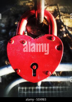 Lock with red heart shape on a bridge - Stock Photo
