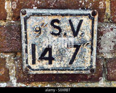 Old water hydrant S.V sign on brick wall - Stock Photo