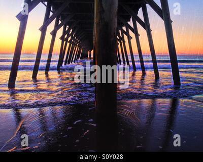 Sunrise viewed under the Myrtle Beach State Park pier in Myrtle Beach South Carolina. - Stock Photo
