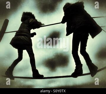Two girls in silhouette balancing on rope walk - Stock Photo