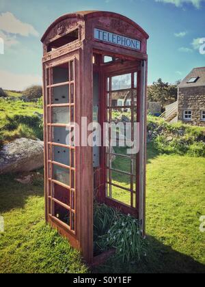 Old overgrown red telephone box on Bryher, Isles of Scilly, Cornwall, England, UK - Stock Photo