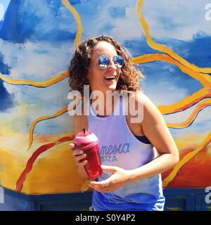 Woman smiling and holding healthy beverage - Stock Photo
