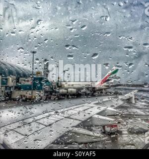 Parked Emirates Airline's plane seen through the rainy aircraft window at Dubai International Airport - Stock Photo