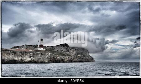 Europa Point lighthouse Gibraltar with clouds swirling around the rock, from sea - Stock Photo