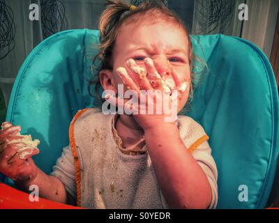 Baby eating messy face - Stock Photo