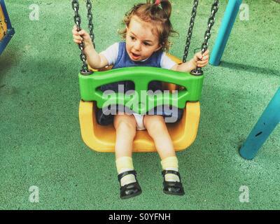 Baby girl on the swing - Stock Photo