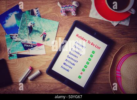 A flat lay desk top with a 'To Do List' on a tablet as a person is organising their holiday or vacation. Looking - Stock Photo