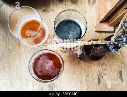 View from above of 3 different types of craft beer on a wooden table with decorative dried wheat and flowers on - Stock Photo