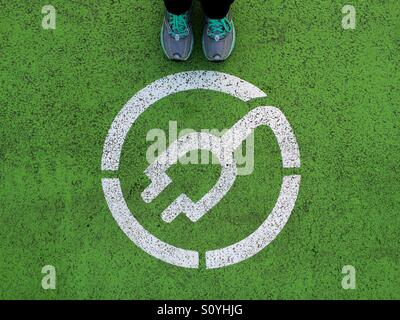 Standing next to electric car recharging point sign - Stock Photo
