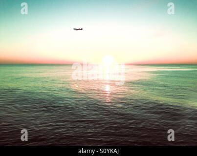 A jet is coming in for a landing at a nearby airport as it flies over the Atlantic Ocean during sunrise. - Stock Photo