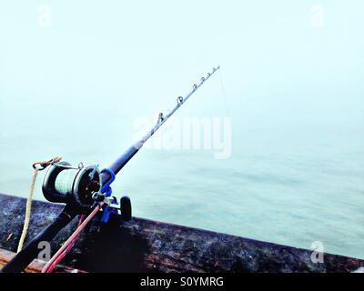 Fishing pole at the end of a fishing pier during sunrise on a dense heavy fog morning overlooking the Atlantic Ocean. - Stock Photo