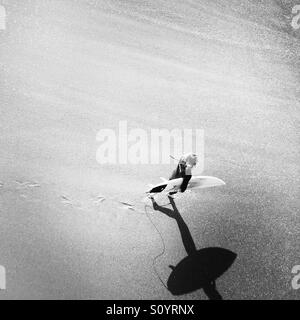A male surfer walks into the surf. Manhattan Beach, California USA. - Stock Photo