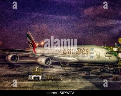 Emirates airplane at the Dubai International Airport gate - Stock Photo