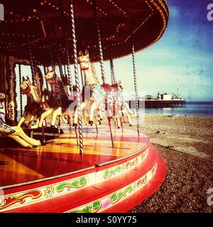 Old style carousel on brighton beach with pier in background - Stock Photo