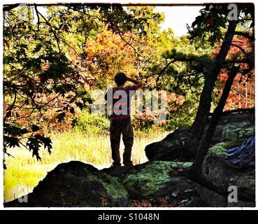 Teen boy looks out on fall landscape. Fall foliage, New England. CT, USA - Stock Photo