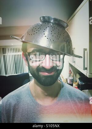 Silly boy with a helmet colander on his head - Stock Photo