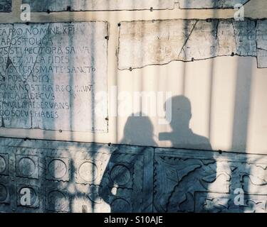 Shadow of a couple on vacation in Rome, Italy, with evening light and fragments of Ancient Rome in Trastevere. Stock Photo