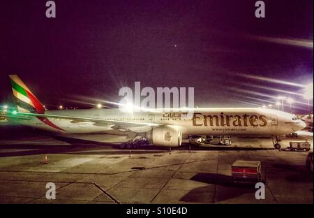 Emirates Airline airplane parked at the stand of Dubai International Airport - Stock Photo