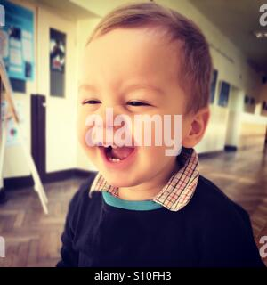 Happy baby boy laughing, having a great time in school - Stock Photo