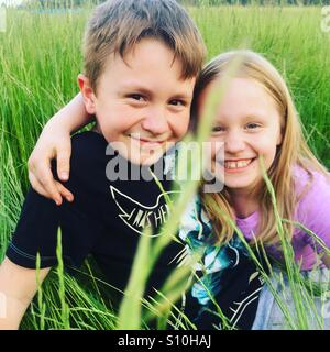 Happy siblings hugging each other and smiling, sitting outside in a tall green grass on a fine, beautiful, sunny, - Stock Photo
