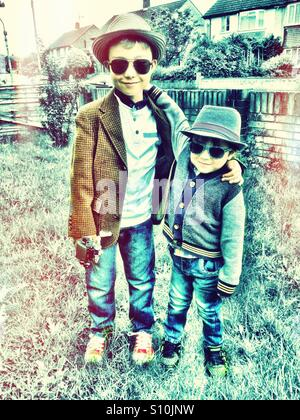 Young brothers wearing hats and sunglasses. - Stock Photo