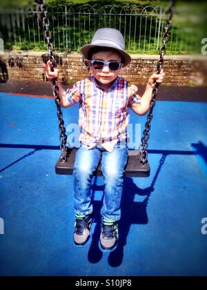 A young boy wearing hat and sunglasses plays on swing in the park. - Stock Photo