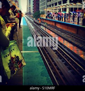 Commuters wait for the train on a rainy afternoon in Chicago - Stock Photo