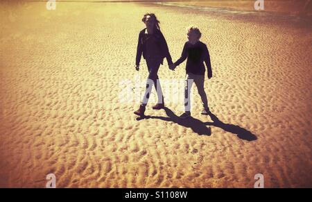 Two girls walking hand in hand along the beach - Stock Photo