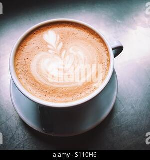 An overhead close-up shot of a fresh latte coffee beverage on a metal table top surface. A simple, clean composition. - Stock Photo