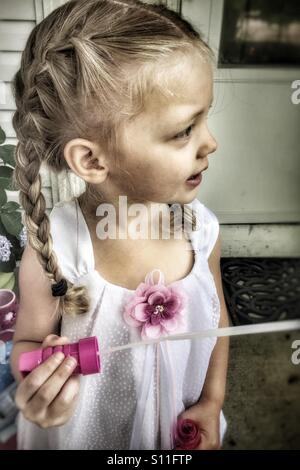 Little girl with French braids playing with bubbles - Stock Photo
