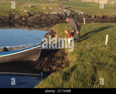Father and son look at a wooden fishing boat tied up in a small stream in Ireland. Traditional Irish curragh is - Stock Photo