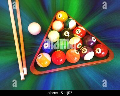 Rack of balls, cue ball and cue sticks for a game of pool - Stock Photo