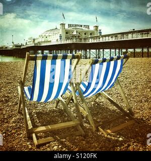 Blue and white striped deckchairs on brighton beach - Stock Photo