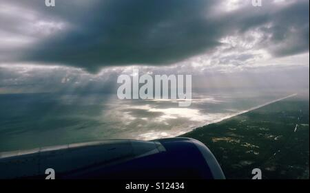 The view from the plane; sun rays from the clouds into the ocean, Kerala India. - Stock Photo