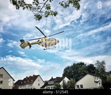 Rescue Helicopter of the ADAC during take off in a residential area during rescue mission, Germany Stock Photo