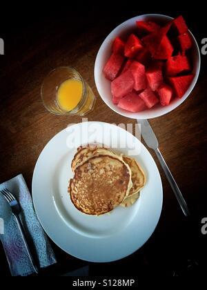 Pancakes, watermelon, and orange juice - Stock Photo