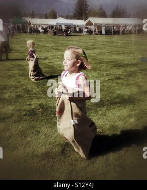 Girls participate in a sack race at a fair. - Stock Photo