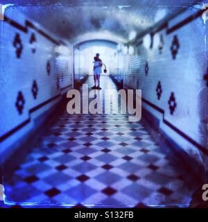 Tunnel of love...a couple hugging in a pedestrian tunnel with Art Deco tiles - Stock Photo