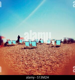 Deckchairs on Brighton beach in the English summer - Stock Photo