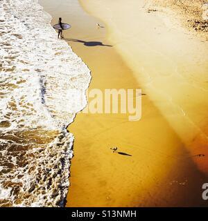 A male Surfer walks up the beach after surfing. Manhattan Beach, California USA. - Stock Photo