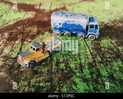 Vintage Matchbox cars on a grungy metal surface - Stock Photo